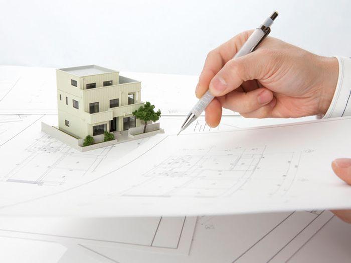 家の模型と設計図に加筆する男性