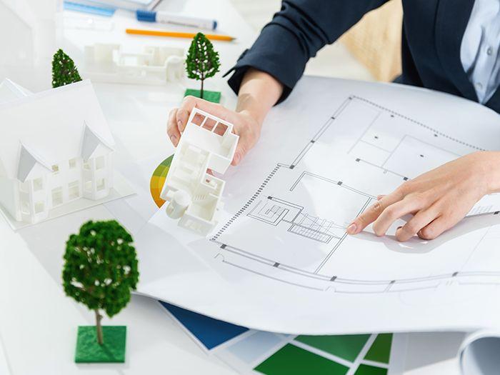 設計図を見ながら家の模型を持つ男性